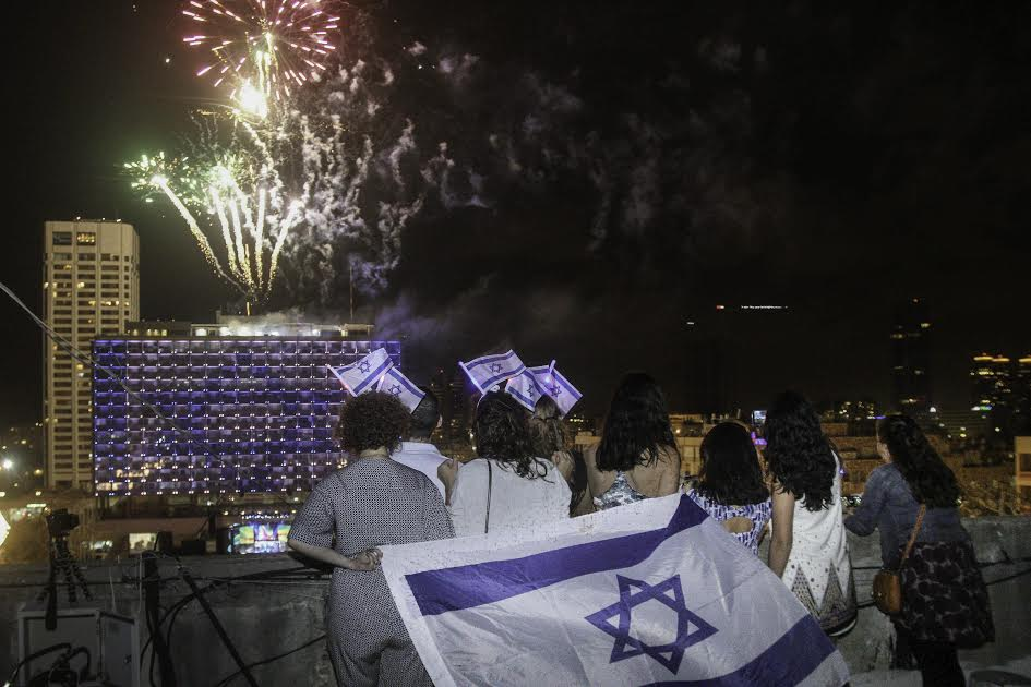 Watching the fireworks from a roof with Israeli flags. Photo: Roni Schutzer/Israel Sun