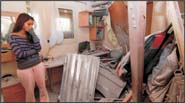 Frustrated Israeli inspects the damage to her home hit by a Hamas rocket in Southern Israel last month. Photo: Eddie Israel/Israel Sun